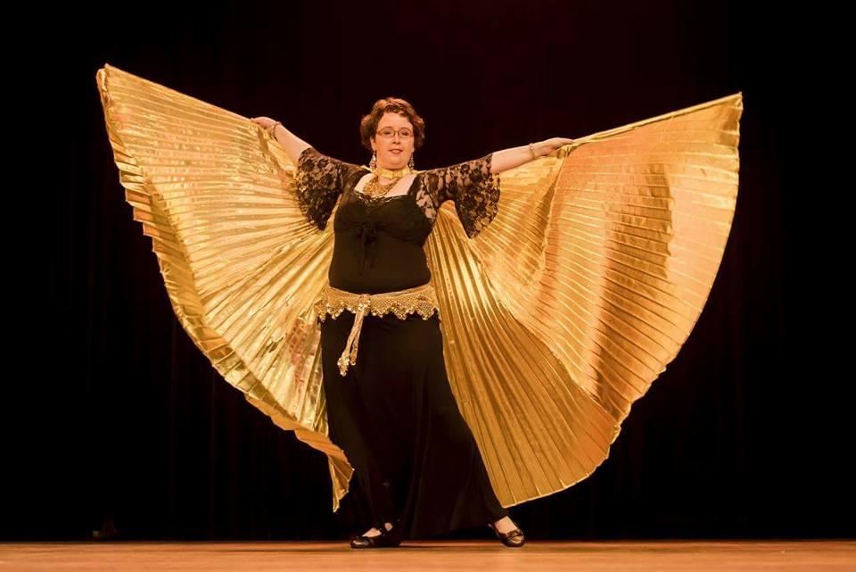 Esther in een zwarte dansjurk met goudkleurige heupsjaal en Wings