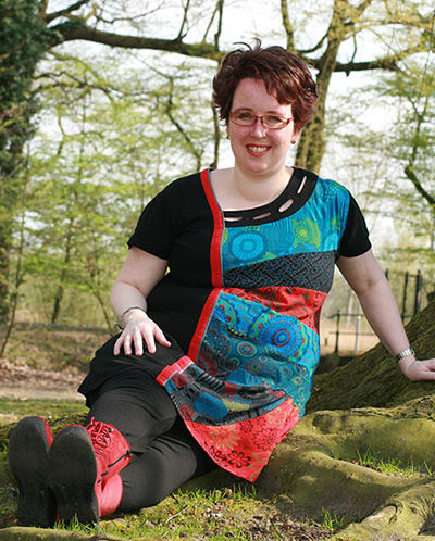 Esther in het bos, zittend op de grond.
